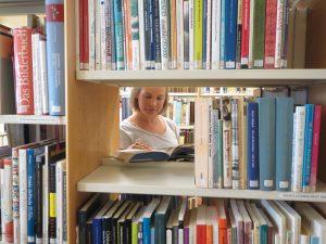 Tutkimuskirjallisuutta, tyhjän hyllyn välistä näkyy asiakas lukemassa kirjaa.