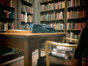 Vanhojen kirjojen kokoelma ja pöytä jolla on vanha kirjoituskone.
