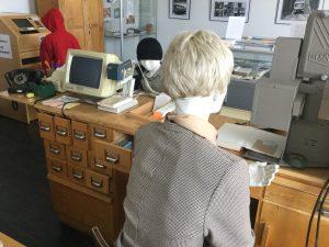 Kirjastomuseon palvelutiski, jossa mallinuket kirjastonhoitajana ja asiakkaina.