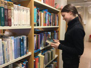 Harjoittelija Noora Raiskio kirjaston hyllyjen ääressä.