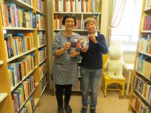 Kaksi henkilöä näyttää Tove Janssonin kirjoja kirjaston hyllyjen edessä. Taustalla iso Muumi-pehmolelu.