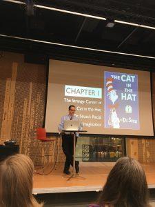 Professori Philip Nel puhuu klassikoista, taustalla näkyy dia, jossa esitellään kirjaa The Cat in the Hat.