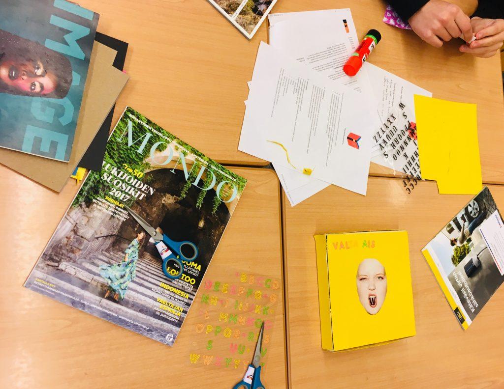 Työpajan askartelutarvikkeita pöydällä: sakset, lehti, ohjepapereita, tarroja, keskeneräinen kirjankansi.