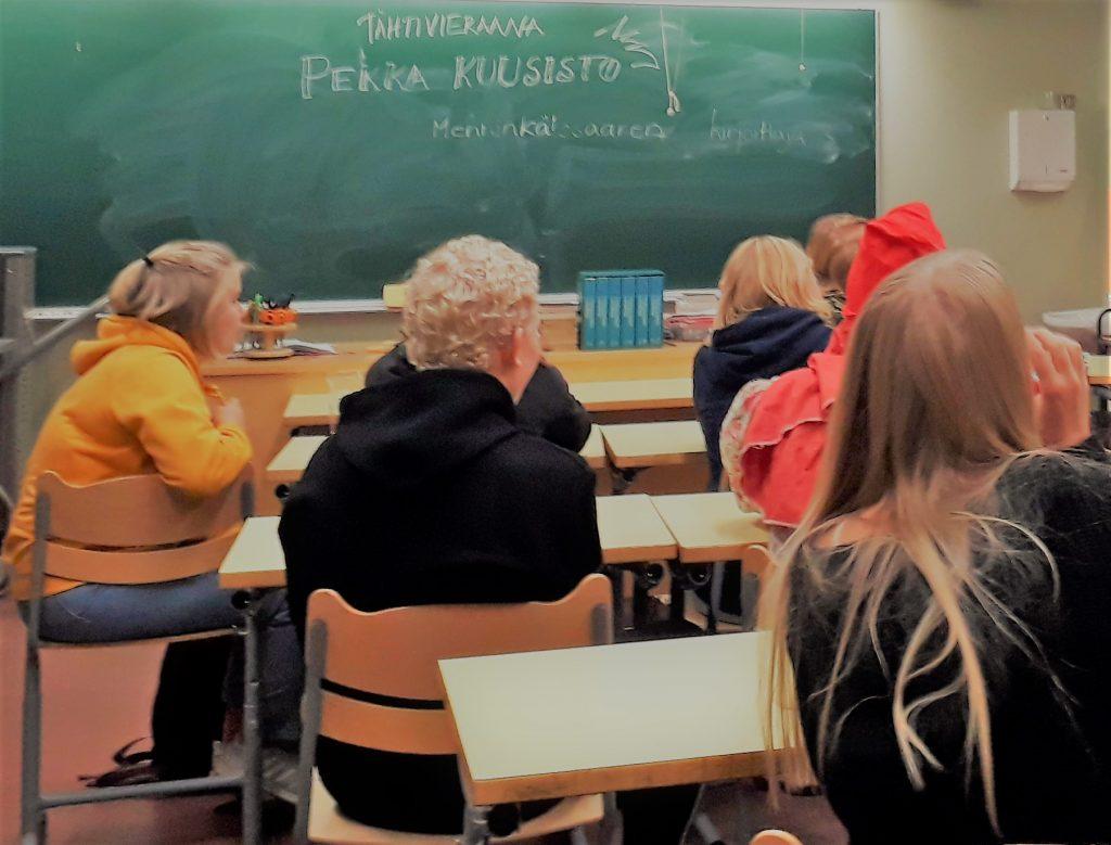 """Nuoria luokkahuoneessa pulpettien ääressä. Liitutaululla lukee """"Tähtivieraana Pekka Kuusisto""""."""