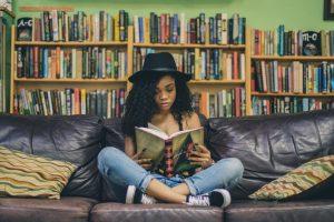 tyttö lukee kirjaa. taustalla näkyy kirjahylly.