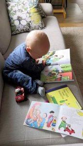 Pieni lapsi istuu sohvalla ja tutkii kirjaa. Vieressä kaksi muuta kirjaa.