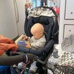 Lapsi istuu rattaissa raitiovaunussa ja lukee kirjaa.