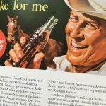 Mies, jolla on hattu päässä, juo pullosta Coca-Colaa ja hymyilee.