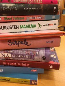 Kirjapino, näkyvissä kymmenen suurimman kustantajan logot kirjoissa.