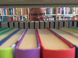 Kirjastonhoitaja kurkistaa kirjahyllyjen välistä.
