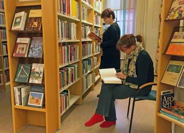 Kaksi naista lukee kirjoja hyllyjen välissä.