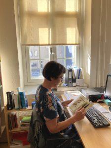 Kuvassa tutkija selaa kirjaa työpöydän ääressä ikkunan edessä.