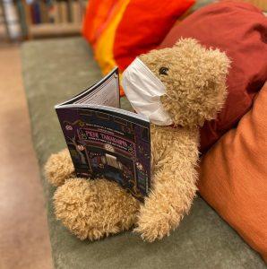 Nalle istuu sohvalla kasvomaski suun ja nenän edessä ja kirja sylissä.