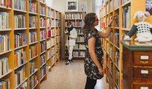 Kaksi naista on kirjaston hyllyjen välissä selaamassa ja lukemassa kirjoja.