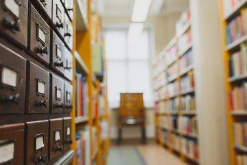 Kuvassa vanha kirjastokortisto sekä kirjaston hyllyjä.