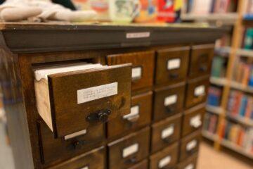 Vanha kirjastokortisto, jonka yksi laatikko on avoinna.